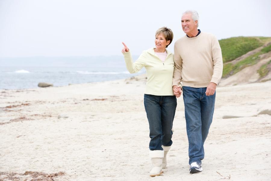 senior-couple-walking-along-beach_Htphq0rs